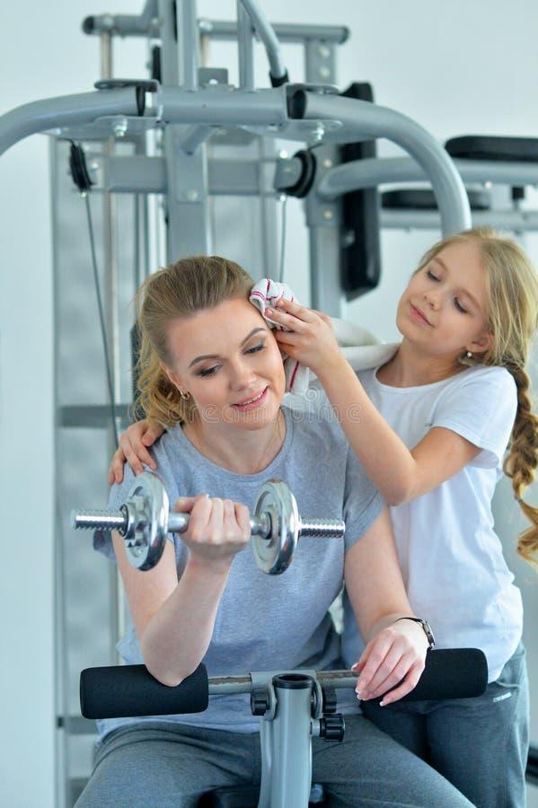 Portret van sportieve jonge vrouw en haar dochter die met domoor in gymnastiek opleiden royalty-vrije stock afbeeldingen