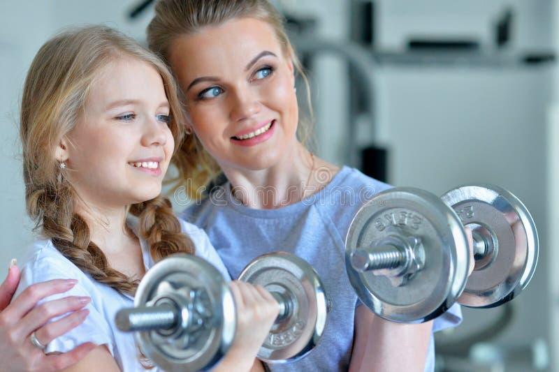 Portret van sportieve jonge vrouw en haar dochter die met domoren in gymnastiek opleiden stock afbeeldingen