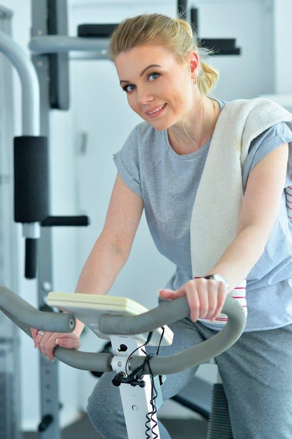 Portret van sportieve jonge vrouw het luisteren muziek tijdens opleiding in gymnastiek stock afbeelding