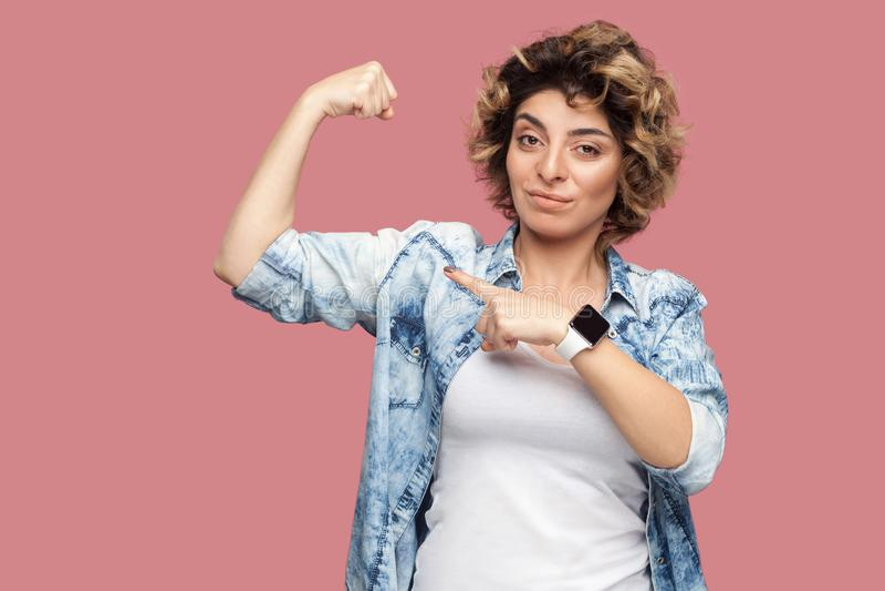 Portret van sterke trotse jonge vrouw met krullend kapsel in toevallig blauw overhemd die en zich op haar bicepsen bevinden richt stock foto's