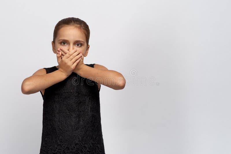 Portret van stil protesterend jong meisje in zwarte kleding dat op witte achtergrond wordt geïsoleerd De handen van meisjesvouwen stock fotografie