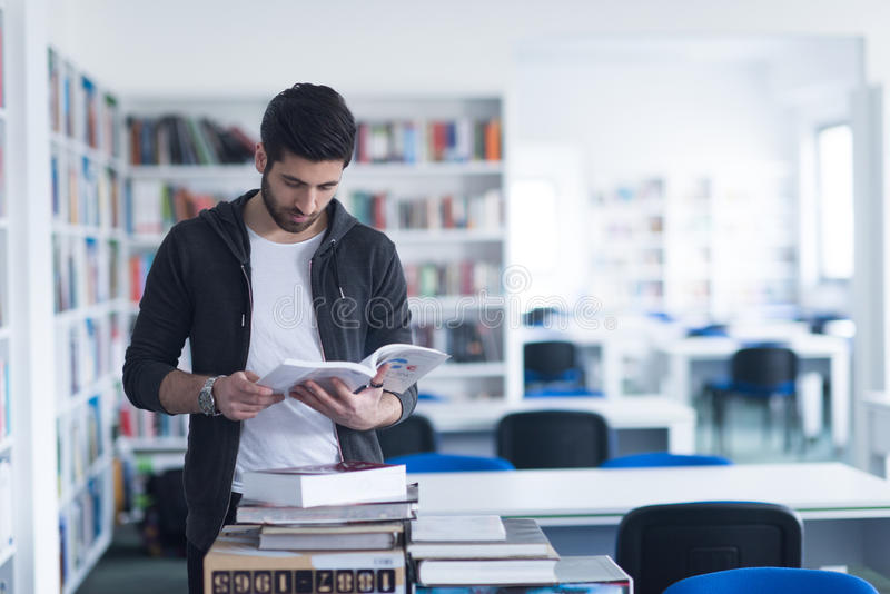 Portret van student terwijl het lezen van boek in schoolbibliotheek stock afbeelding