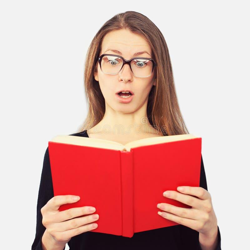 Portret van studentenmeisje in geschokte glazen het kijken in boek stock foto