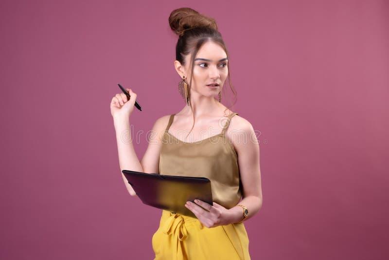 Portret van studentenmeisje met pen en document omslag Jonge mooie arbeider die iets in haar documenten schrijven stock fotografie