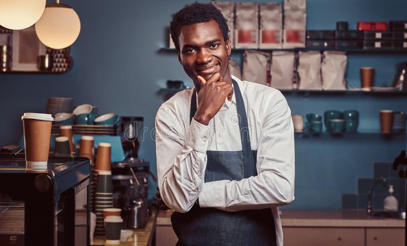 Portret van succesvolle Afrikaanse Amerikaanse eigenaar kleine zaken die bij camera glimlachen terwijl status bij de koffiewinkel royalty-vrije stock foto