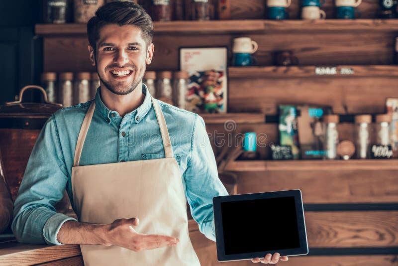 Portret van succesvolle barista in schort met tablet in koffie stock fotografie