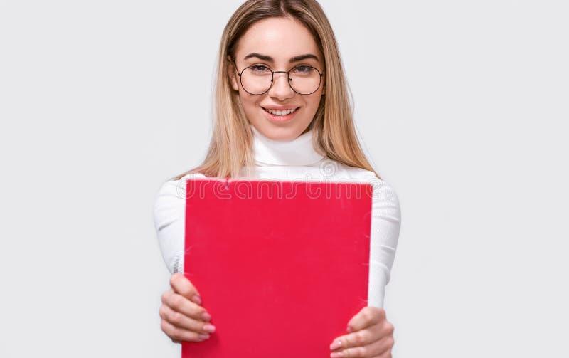 Portret van succesvolle jonge studente die witte blouse en ronde transparante oogglazen met rode omslag in handen dragen stock foto