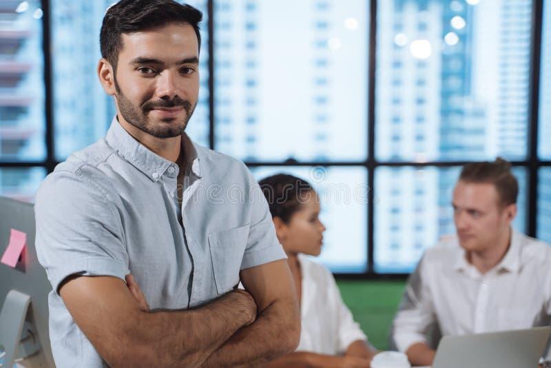 Portret van succesvolle jonge zakenman op kantoor, collega's op achtergrond stock foto