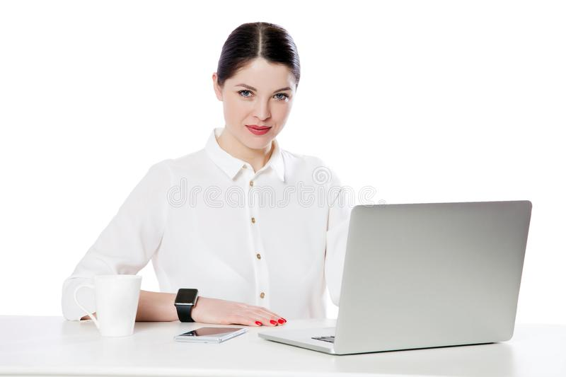 Portret van succesvolle kalme aantrekkelijke donkerbruine onderneemster met make-up in witte overhemdszitting met laptop en het b stock foto's