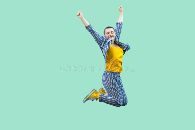 Portret van succesvolle mooie korte haar jonge modieuze vrouw in toevallig gestreept kostuum die en haar overwinning springen cel stock foto's