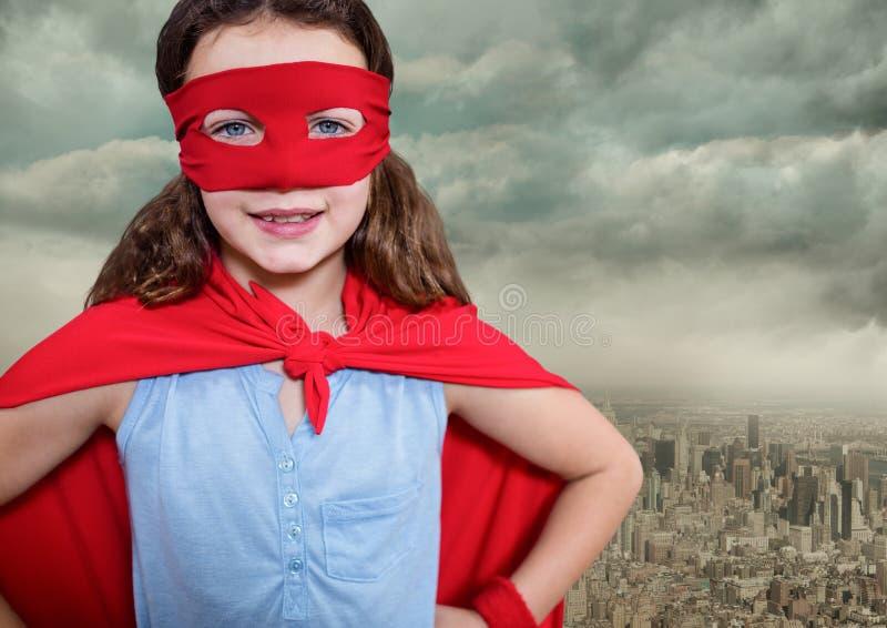 Portret van super meisje rood masker dragen en kaap die zich met hand op heup tegen cityscape backgro bevinden royalty-vrije stock foto