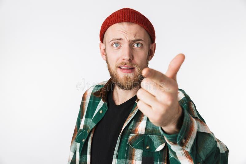 Portret van tevreden gebaarde kerel die hoed en plaidoverhemd dragen die duim tonen, terwijl status geïsoleerd over witte achterg royalty-vrije stock fotografie
