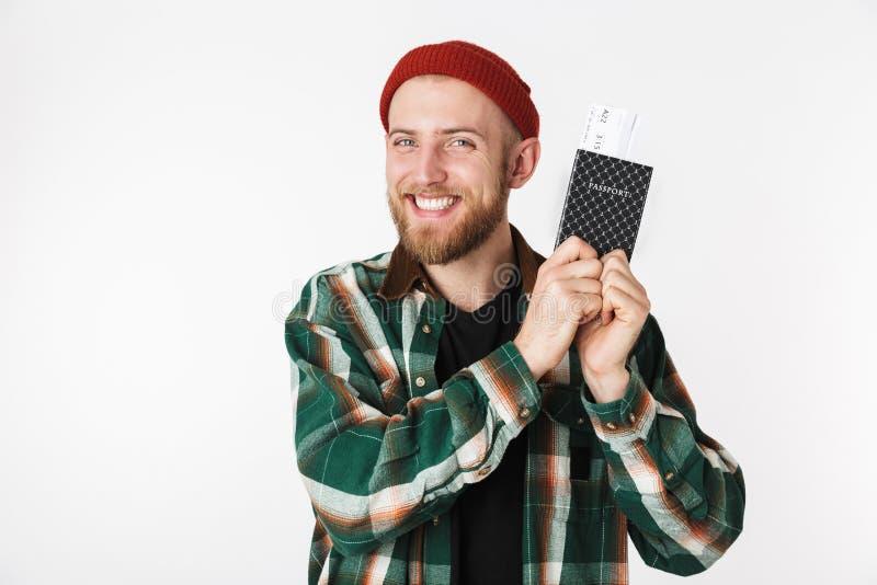 Portret van tevreden kerel die hoed en plaid het paspoort en de reiskaartjes dragen van de overhemdsholding, terwijl status geïso stock foto's