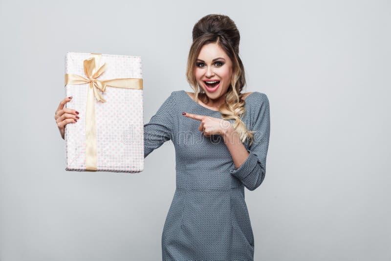 Portret van tevreden mooie jonge vrouw in toevallige stijl die en vinger bevinden zich richten om met gele boog voor te stellen e stock fotografie