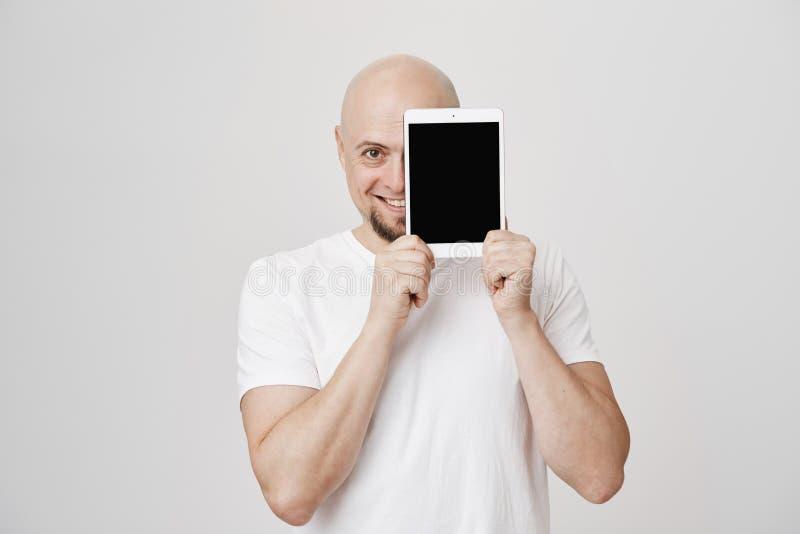 Portret van tevreden volwassen Kaukasisch mannelijk model met baard die de helft van gezicht behandelen met tablet terwijl het re royalty-vrije stock foto