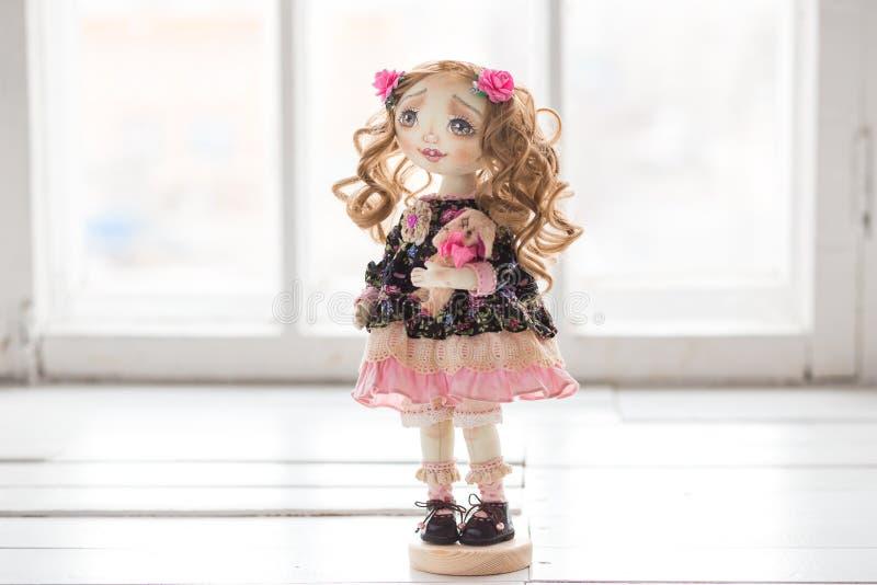 Portret van textiel met de hand gemaakte uitstekende pop met groene ogen, lang bruin krullend haar in lichtrose en blauwe textiel royalty-vrije stock foto