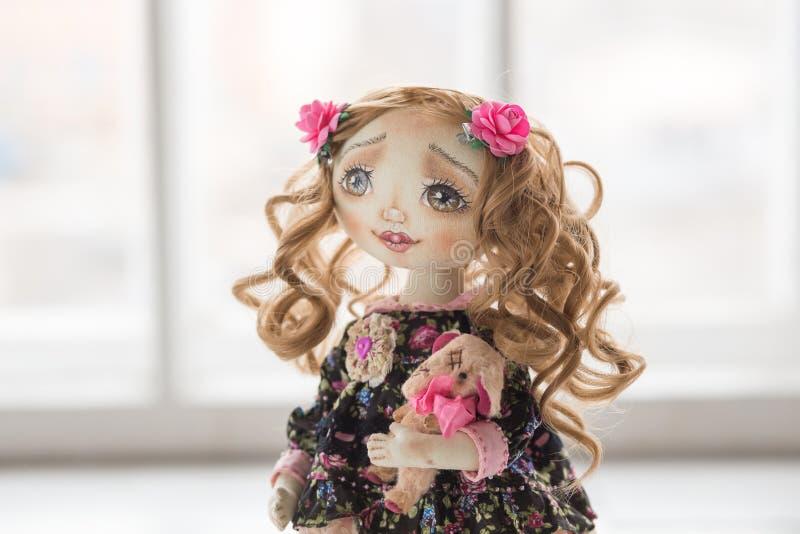 Portret van textiel met de hand gemaakte uitstekende pop met groene ogen, lang bruin krullend haar in lichtrose en blauwe textiel royalty-vrije stock foto's