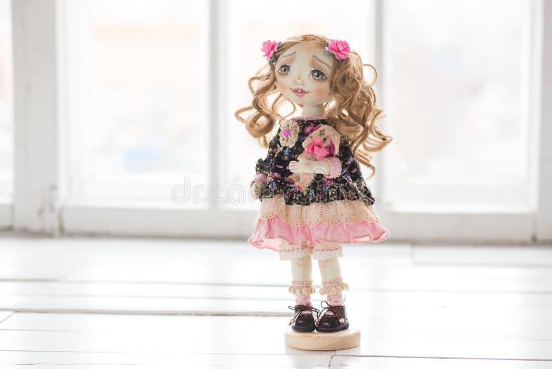 Portret van textiel met de hand gemaakte uitstekende pop met groene ogen, lang bruin krullend haar in lichtrose en blauwe textiel stock foto's