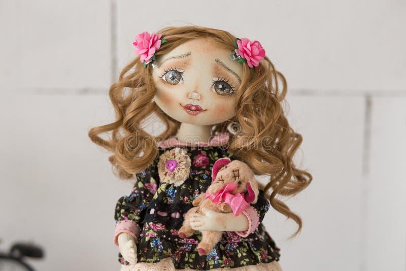 Portret van textiel met de hand gemaakte uitstekende pop met groene ogen, lang bruin krullend haar in lichtrose en blauwe textiel stock foto