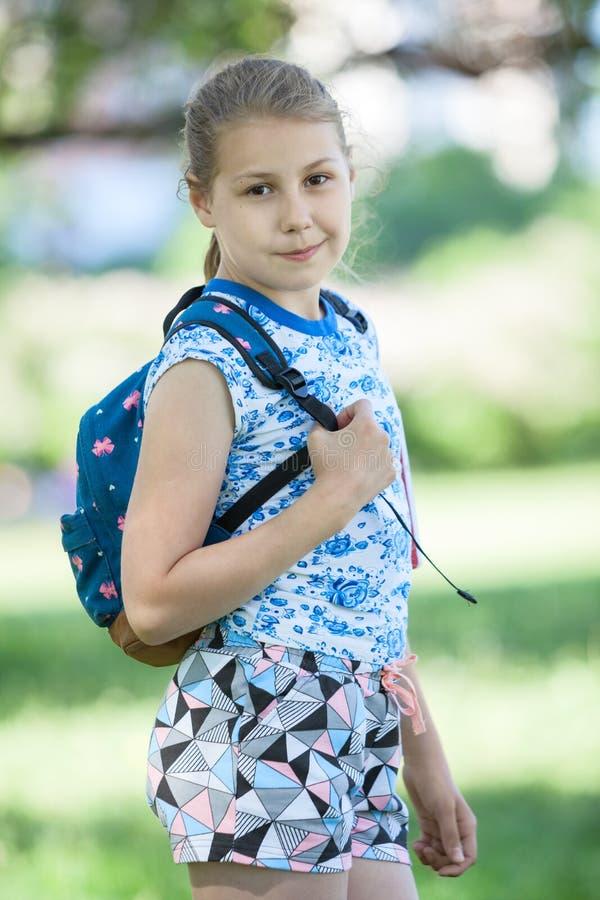 Portret van tien éénjarigenmeisje met kleine rugzak op achter haar, de zomertuin stock afbeelding