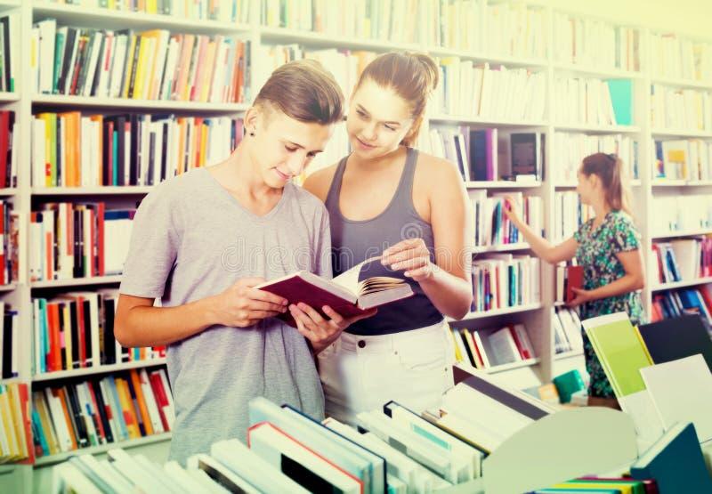 Portret van tiener en meisjesklanten die open boek bekijken royalty-vrije stock afbeeldingen