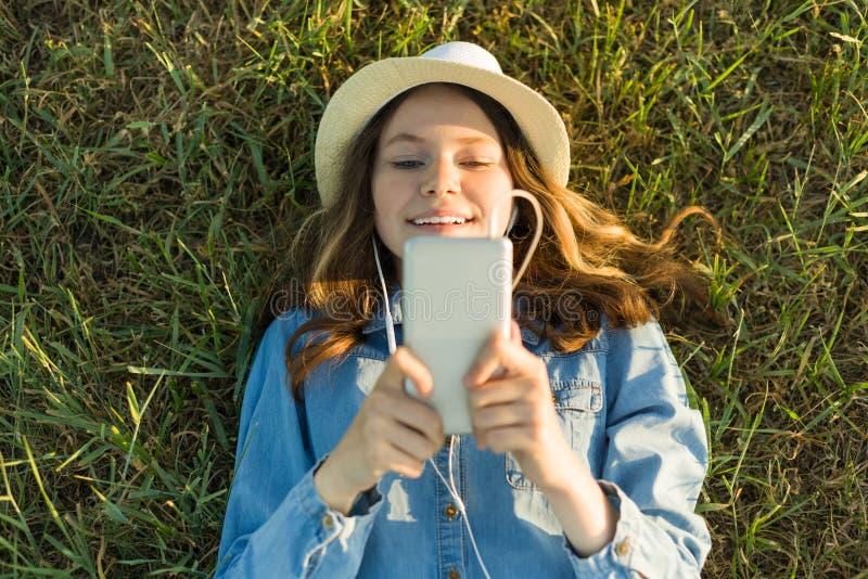 Portret van tiener 14 jaar het oude liggen op het gras Het meisje in kledingshoed, in haar hoofdtelefoons houdt een smartphone, l stock foto's