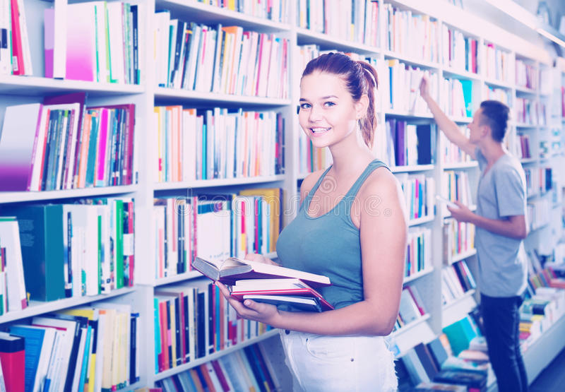 Portret van tienerklant die open boek status bekijken stock afbeeldingen