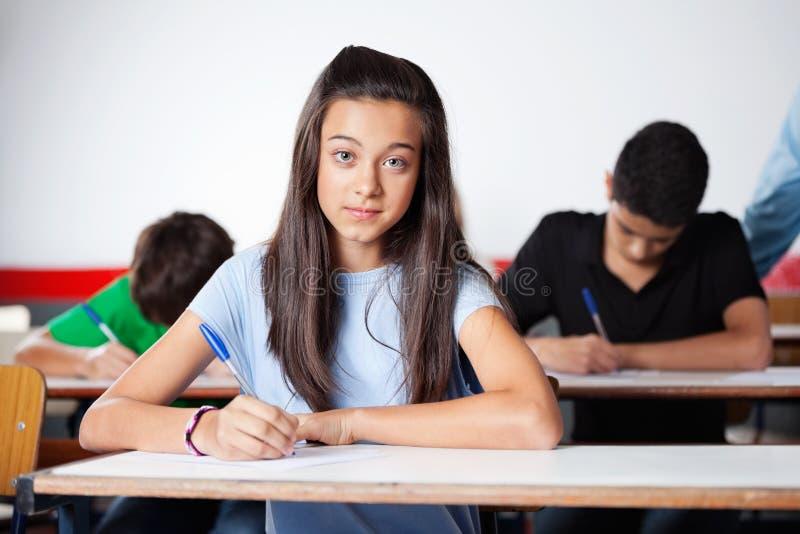 Portret van Tienerschoolmeisje die bij Bureau schrijven royalty-vrije stock foto