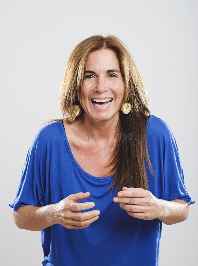 Portret van toothy glimlachende volwassen vrouw met bruin recht haar en grote kleurrijke oorringen stock foto