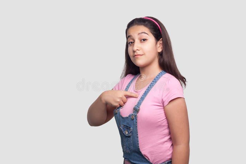 Portret van trots ernstig mooi donkerbruin meisje in toevallige roze, richten en t-shirt en blauwe overall die eruit zien bevinde stock afbeeldingen