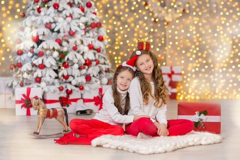 Portret van twee één jonge meisjeszusters dicht bij witte groene Kerstboom De meisjes in mooie avondjurkenkleren in Nieuw royalty-vrije stock fotografie