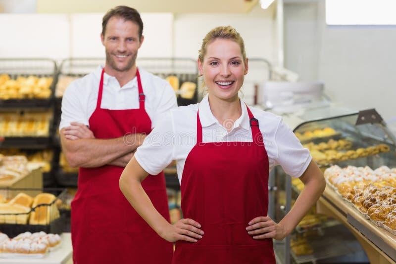 Portret van twee bakkers met handen op heupen royalty-vrije stock foto's