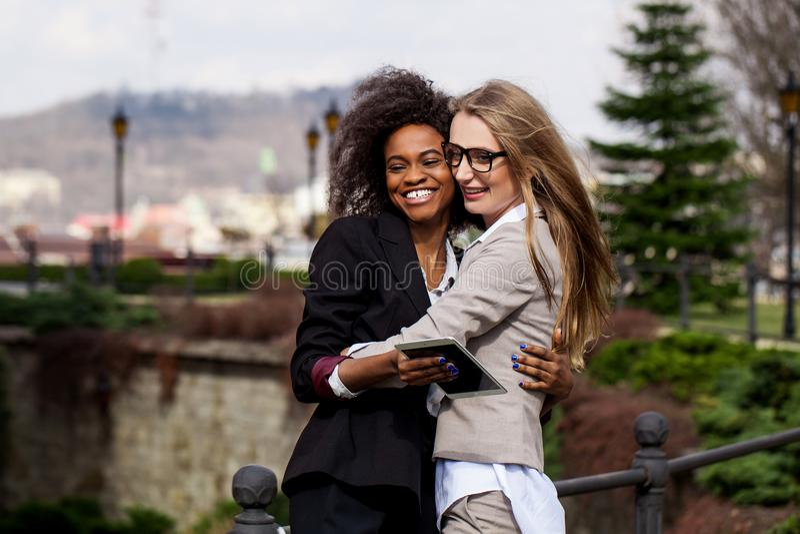 Portret van twee charmante glimlachende onderneemsters die in het park koesteren stock afbeeldingen