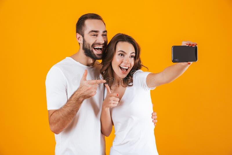 Portret van twee de donkerbruine mensenmens en vrouw die selfie foto op smartphone nemen, dat over gele achtergrond wordt geïsole royalty-vrije stock afbeeldingen