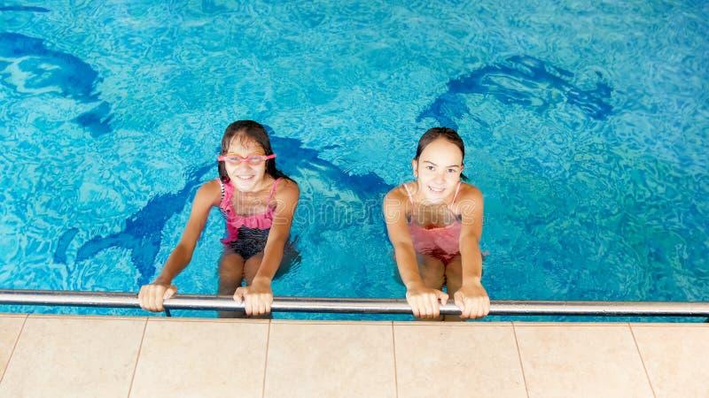 Portret van twee gelukkige glimlachende tieners in het binnen zwembad royalty-vrije stock fotografie