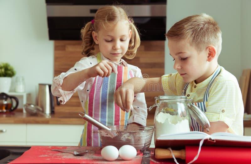 Portret van twee gelukkige kinderen die dat pret hebben tijdens het koken c stock fotografie