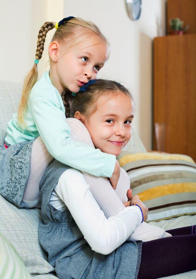 Portret van twee gelukkige kleine zusters die binnen spelen royalty-vrije stock foto