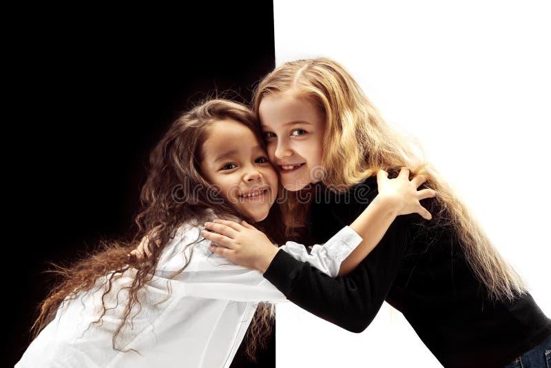 Portret van twee gelukkige meisjes op een witte en zwarte achtergrond stock foto