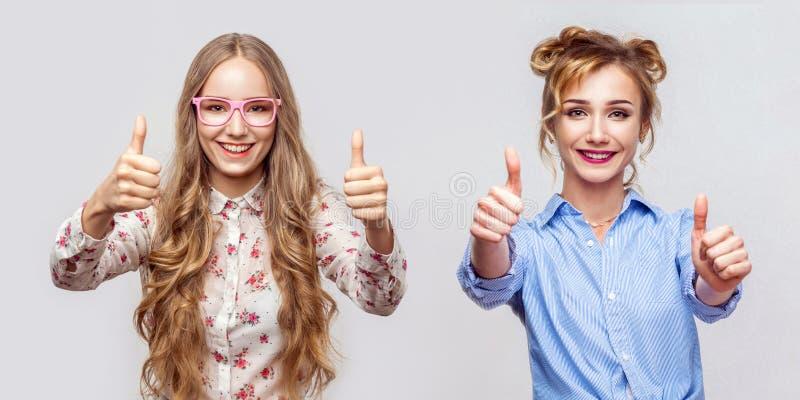 Portret van twee gelukkige mooie blonde jonge vrouw in toevallige stijl met make-up en kapsel die, duimen die, bekijken opstaan royalty-vrije stock foto