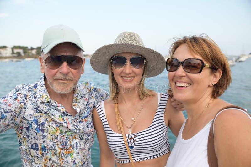 Portret van twee gelukkige vrouwen en een oudere man over kustpromenade het nemen selfie stock fotografie