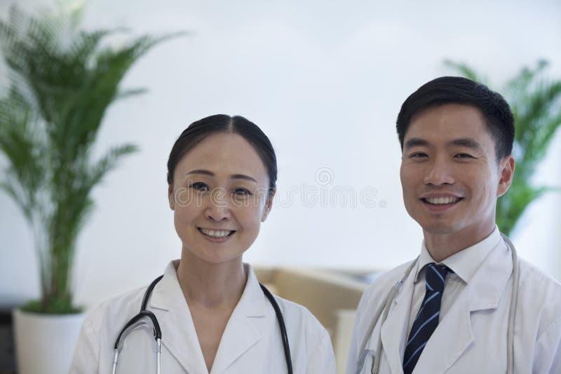 Portret van twee glimlachende artsen in het ziekenhuis stock fotografie