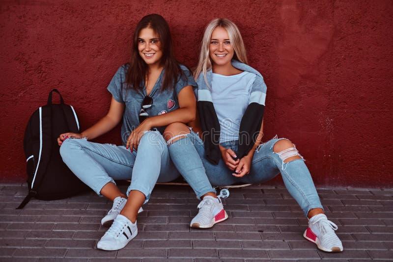 Portret van twee glimlachende hipster meisjes die samen op een skateboard zitten en op een muur bij stoep leunen stock afbeeldingen