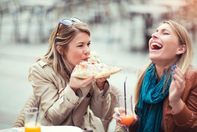 Portret van twee jonge vrouwen die pizza in openlucht eten royalty-vrije stock afbeelding