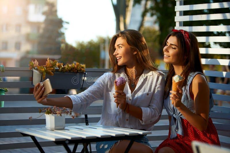 Portret van twee jonge vrouwen die samen het eten van roomijskegels en binnen het nemen van selfie foto op cellphonecamera zitten stock afbeelding