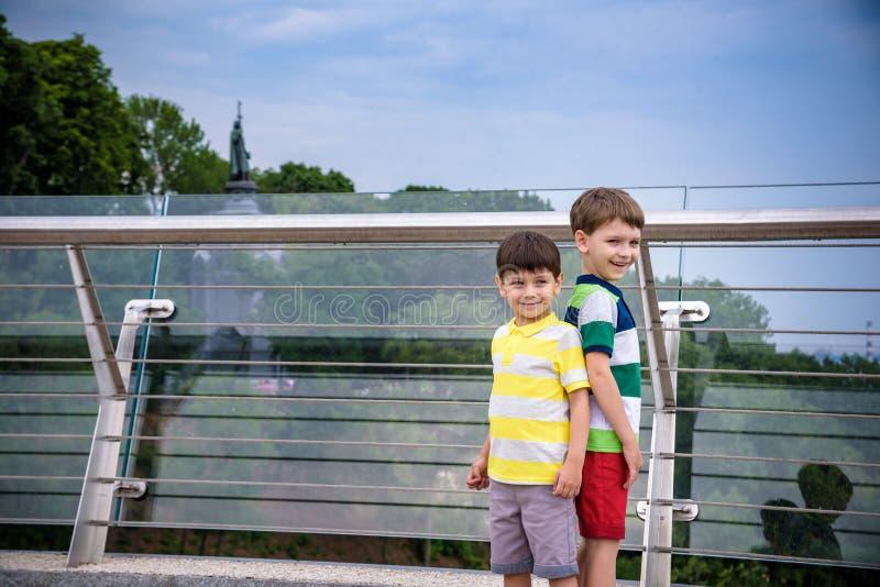 Portret van twee jongensjong geitje een gang over een brug en neer het kijken, kind die buiten in zonnige dag, Jonge jongens lope royalty-vrije stock afbeeldingen