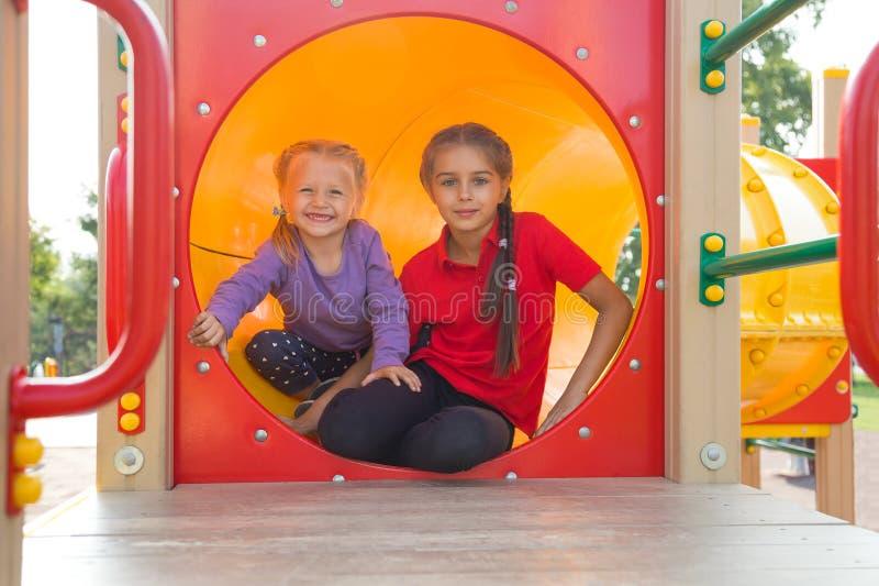 Portret van twee leuke Kaukasische meisjes die op speelplaats in de zomer spelen royalty-vrije stock afbeeldingen