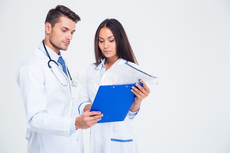 Portret van twee medische arbeiders die klembord bekijken stock afbeelding