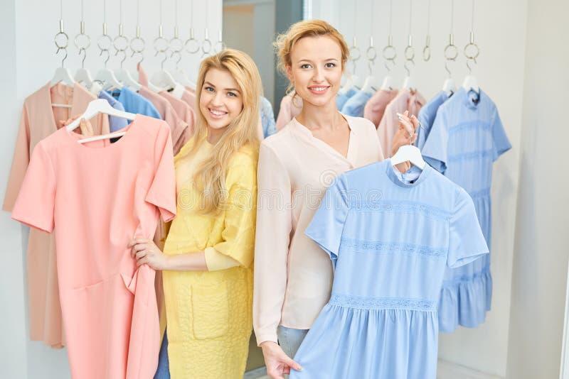 Portret van twee meisjes in een kledingsopslag stock fotografie