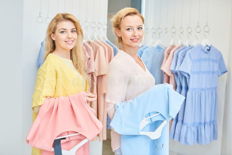 Portret van twee meisjes in een kledingsopslag stock foto's