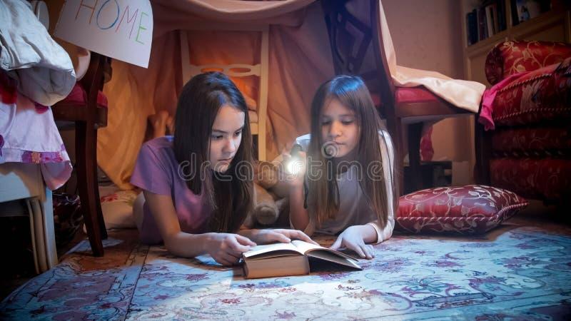 Portret van twee meisjes in pyjama's die op vloer bij slaapkamer liggen en boek lezen bij nacht royalty-vrije stock foto's